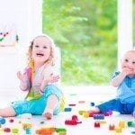 Adorable laughing toddler girl and a funny little baby boy, brother and sister, playing with colorful blocks sitting on a floor in a sunny bedroom with a big window